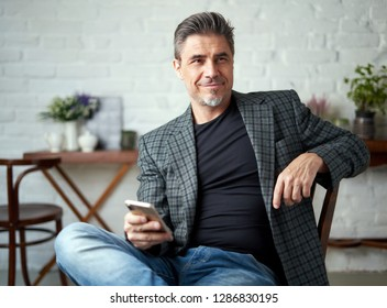 Portrait of happy older white man with gray hair wearing jacket smiling using smart phone. 