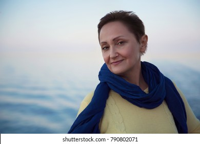 Portrait of happy older woman cruising on a cruise ship liner boat. Beautiful sunset or sunrise blurred background. Summer holidays vacation trip concept.