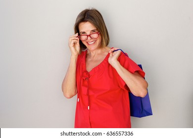Portrait of happy older woman with glasses and shopping bags