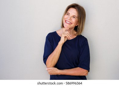 Portrait of happy older woman with hand to chin