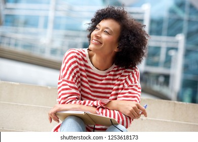 Portrait of happy older woman sitting on steps with book and pen