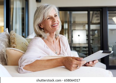 Portrait of happy older woman sitting on sofa with digital tablet