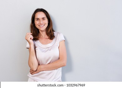 Portrait of happy older woman standing against white background
