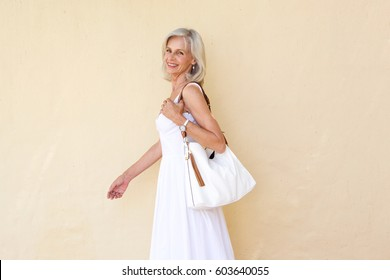 Portrait of happy older woman in summer dress walking with purse