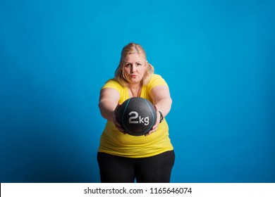 Portrait of a happy overweight woman exercising with a heavy ball in studio.