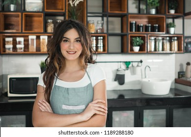 portrait of a happy owner of a cafe or waitress smiling to camera