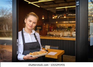 Portrait of happy owner standing at restaurant entrance holding tray of meatballs greeting customers. Young entrepreneur at small family business restaurant inviting people to taste food