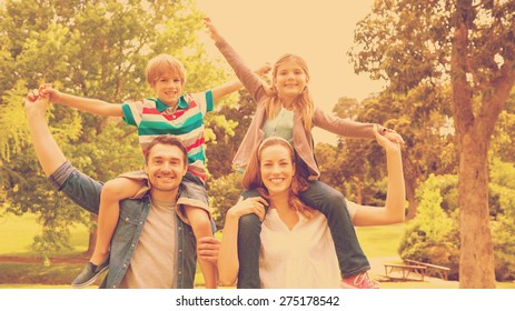 Portrait of happy parents carrying kids on shoulders at the park