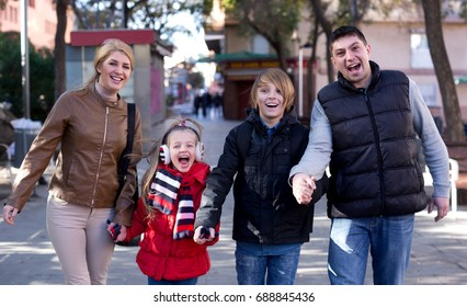 Portrait happy parents with children posing outdoor in cold day and smiling
