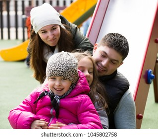 Portrait of happy parents helping kids on slide in autumn day outdoors. Focus on brunette girl