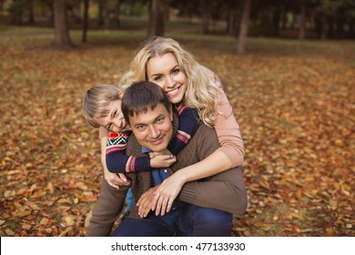 Portrait happy parents with his their son in a park in the autumn