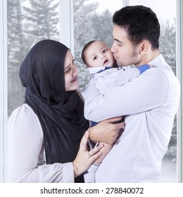 Portrait of happy parents hugging their little baby at home, shot with winter background on the window