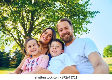 Portrait of happy parents sitting together with children, little boy and girl, in park, looking at camera and smiling