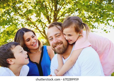 Portrait of happy parents and their children sitting together, looking at camera and smiling in summer
