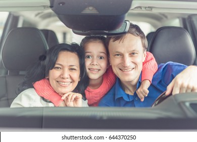 Portrait of happy parents and their cute little daughter hugging smiling to the camera sitting in a car together happiness love family travelling automobile transport emotions expressive parenting