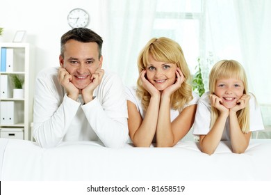 Portrait of happy parents and their daughter looking at camera at home