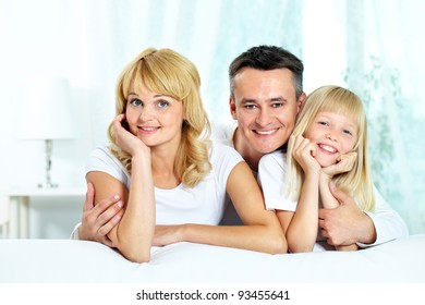 Portrait of happy parents with their daughter spending time at home