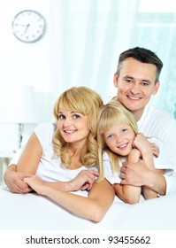 Portrait of happy parents with their daughter looking at camera