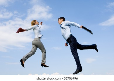 Portrait of happy partners jumping against blue sky
