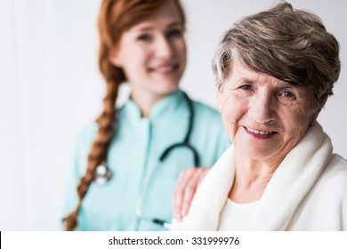 Portrait of happy patient of geriatric ward and female doctor