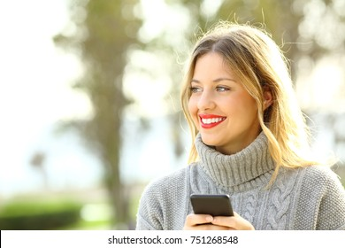 Portrait of a happy pensive girl wearing a sweater looking away and holding a smart phone in winter in a park with copy space