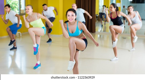 Portrait of happy people dancing zumba in dance class