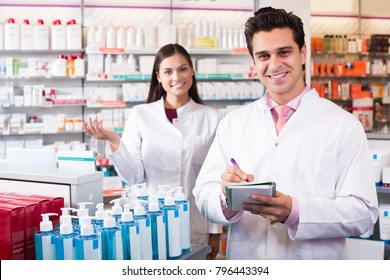 Portrait of happy pharmacist and pharmacy technician posing in drugstore