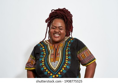 Portrait of happy plump young african american woman lauging with closed eyes on light background. Emotions and feelings concept