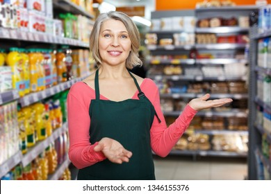 Portrait of happy polite mature saleswoman inviting to grocery store, offering quality food products