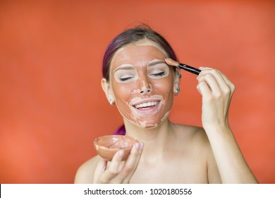 Portrait of a happy and positive beautiful girl applying a tassel and red clay on her face against a red wall. cosmetic procedures. clay face mask.Beauty procedures skin care concept.