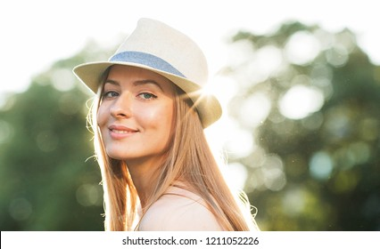 Portrait of a happy and positive beautiful woman with blond hair and wearing a hat looking with a smile at the camera lit by the rays of the setting sun. Summer vacation. Girl in city. City lifestyle