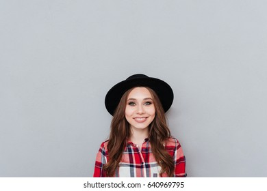 Portrait of a happy positive girl in plaid shirt and hat looking at camera isolated over gray background