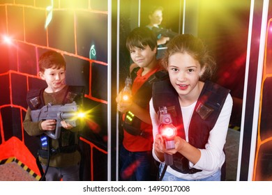Portrait of happy  positive smiling teenager girl with laser gun having fun on dark lasertag arena