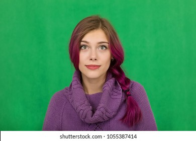 Portrait of a happy and positive young beautiful woman with purple hair and a purple sweater, looking with surprised eyes at the screen on a background of a green wall.European woman LIFESTYLE