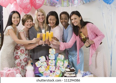 Portrait of happy pregnant woman with female friends at a baby shower