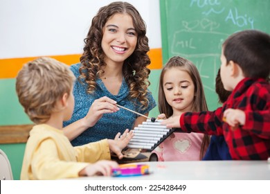 Portrait of happy preschool teacher and children playing with xylophone in classroom
