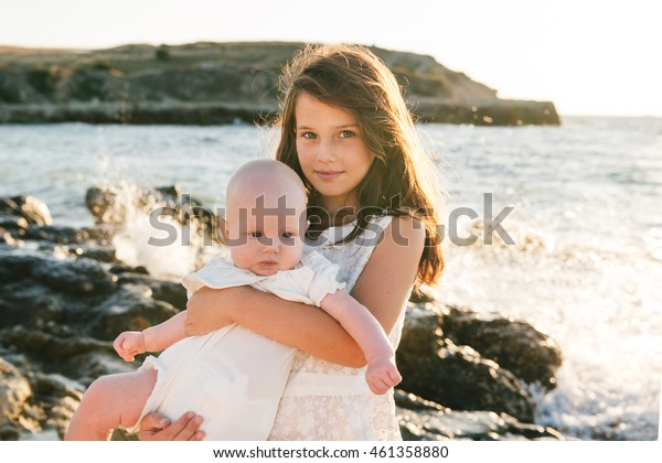 Portrait of happy preteen sister and little baby on the beach