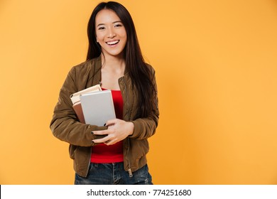 Portrait of a happy pretty asian girl holding books and looking at camera isolated over yellow background