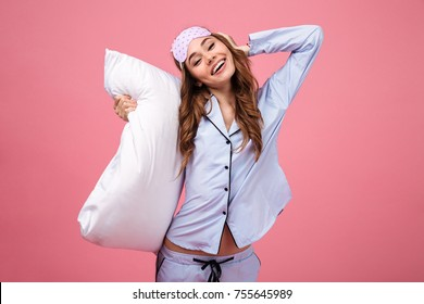 Portrait of a happy pretty girl dressed in pajamas holding pillow and looking at camera isolated over pink background