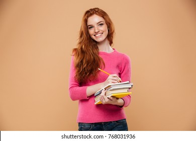 Portrait of a happy pretty redhead girl holding books and a pencil isolated over beige background