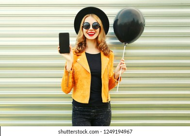 Portrait happy pretty smiling woman showing phone with blank screen holding black helium air balloon in round hat, yellow jacket on metal wall background