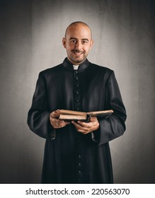 Portrait of  a happy priest that reads a bible