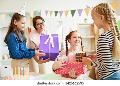 Portrait of happy red haired  girl receiving gifts from friends during Birthday party, copy space