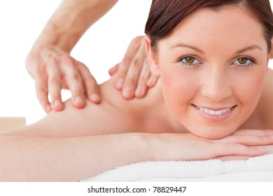 Portrait of a happy red-haired female posing while receiving a massage in a spa