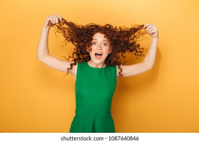 Portrait of a happy redhead woman in dress playing with her hair isolated over yellow background