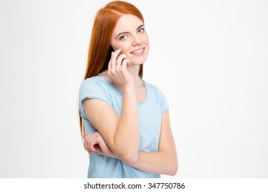 Portrait of a happy redhead woman talking on the phone and looking at camera isolated on a white background