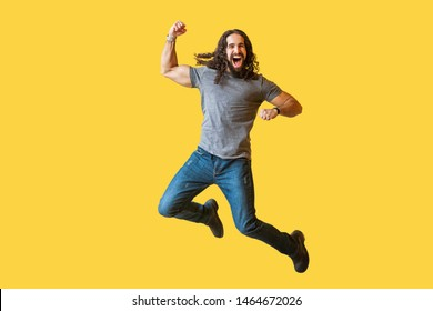 Portrait of happy rejoicing bearded young man with long curly hair in casual grey tshirt jumping and celebrating his vivtory with amazed excited face. indoor studio shot isolated on yellow background.