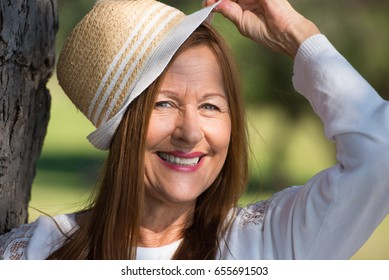 Portrait happy relaxed and attractive mature woman friendly smiling with hat in park outdoors.