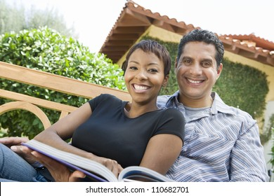 Portrait of happy relaxed couple with a book