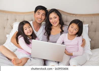 Portrait of a happy relaxed family of four using laptop in bed at home